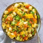 top down view of mango pineapple salsa with a serving spoon