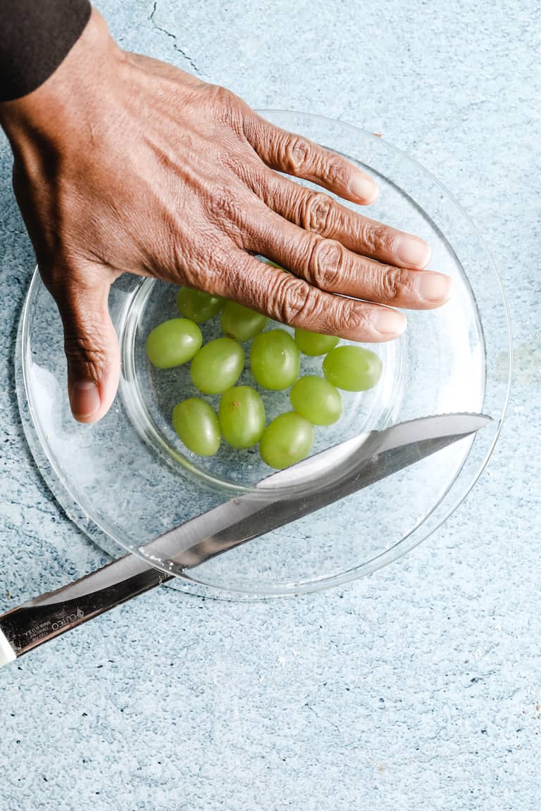 hand slicing grapes in half with serrated knife to be used to make southern grape salad