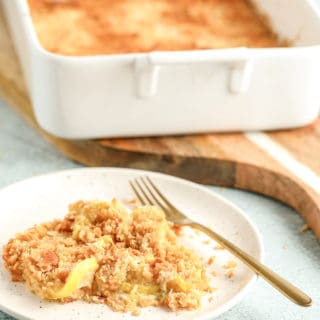 a serving of yellowe squash casserole on a white plate in front of the full casserole dish