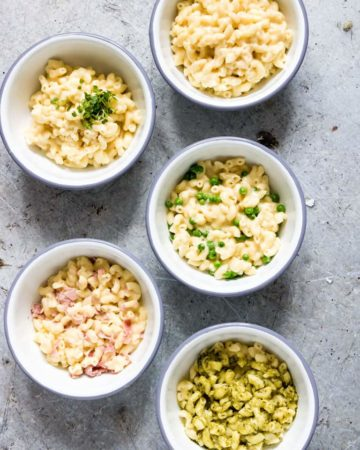 five white bowls with different varieties of instant pot mac and cheese on a countertop