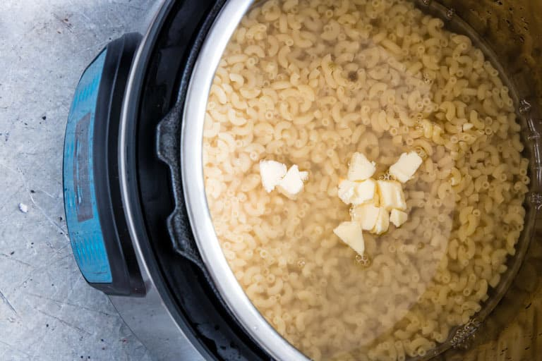 raw instant pot mac and cheese ingredients inside an open instant pot