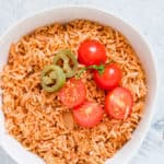 white bowl on a white countertop containing instant pot mexican rice with sliced tomatoes on top