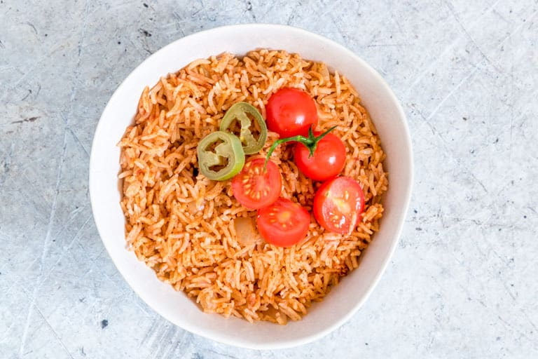 instant pot mexican rice in a white bowl with tomatoes on top