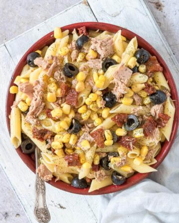 tuna pasta salad served in a red bowl with spoon