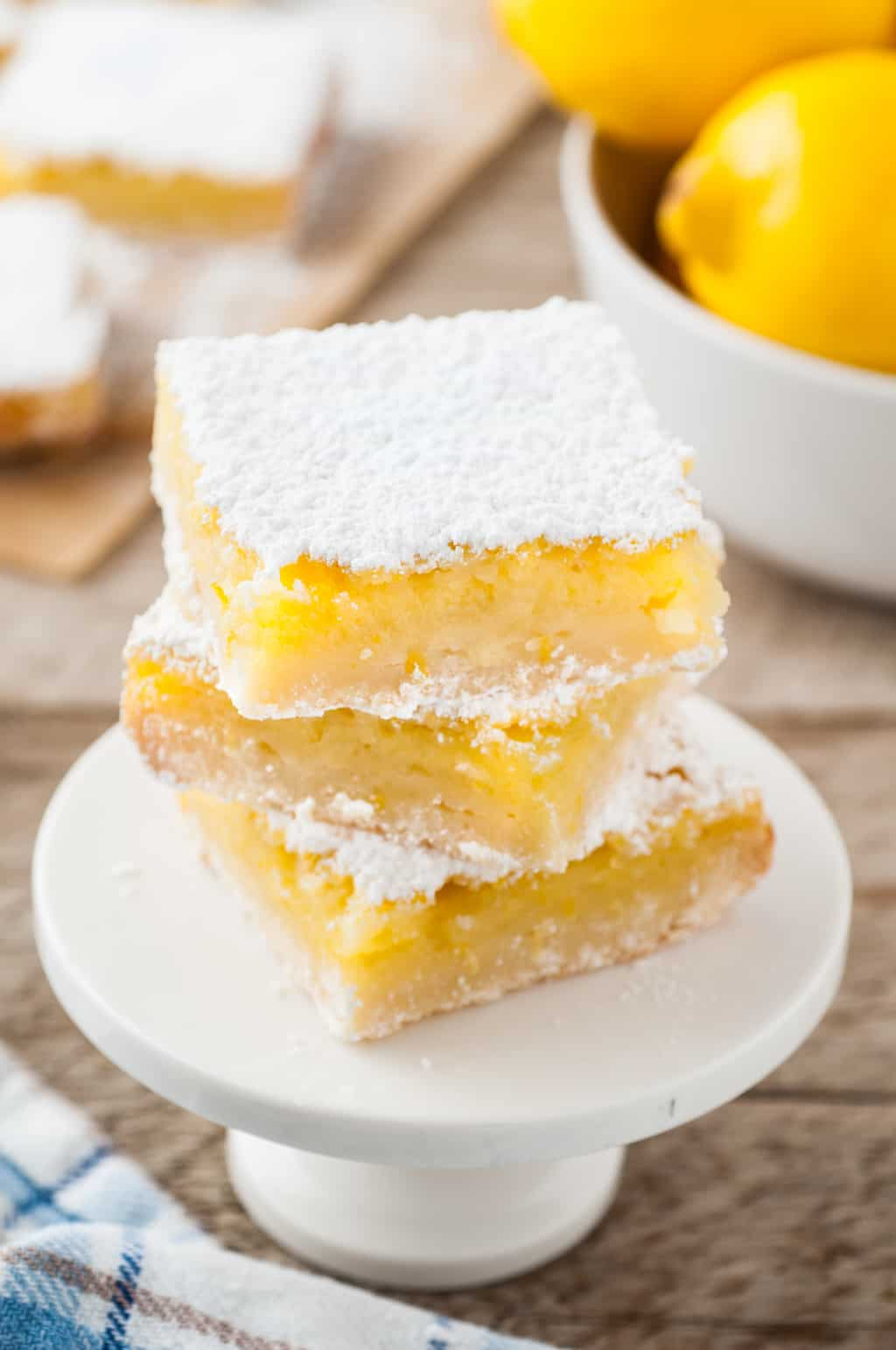 lemon bars stacked on a serving plate and set next to a bowl of lemons