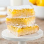 three lemon bars stacked on top of a white cake stand