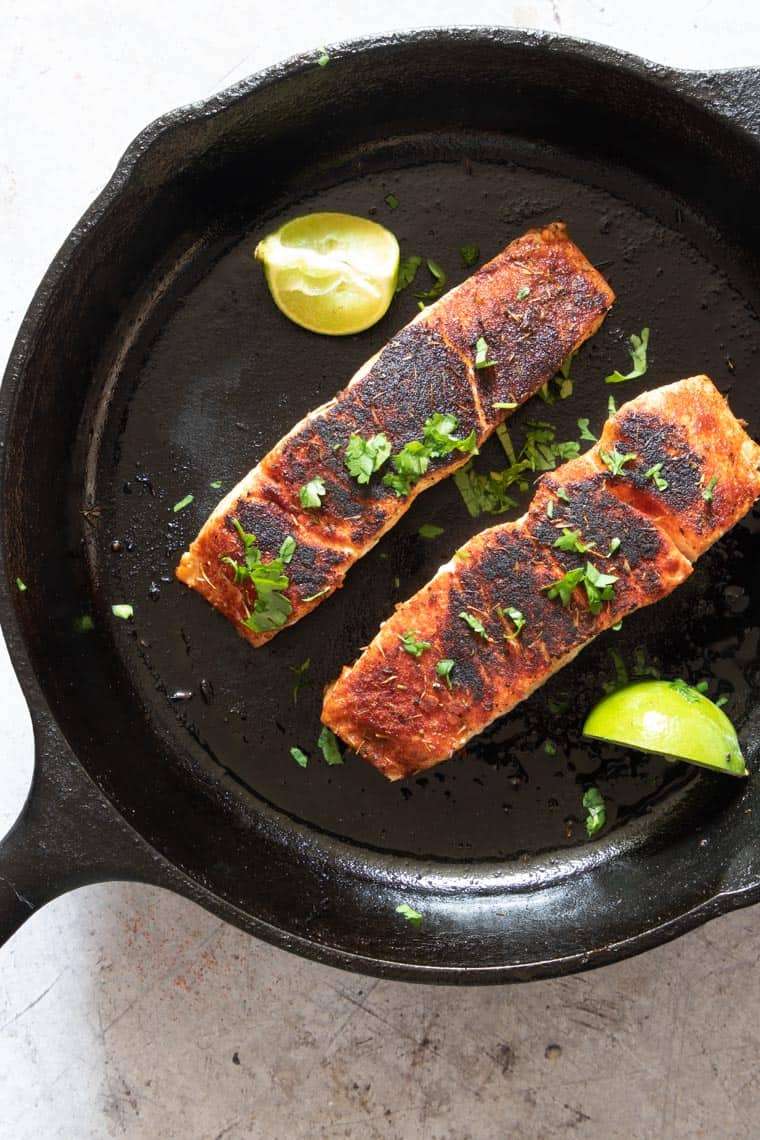 two portions of blackened salmon inside a skillet