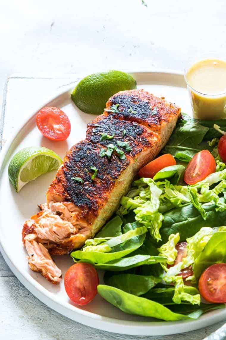 close up view of finished blackened salmon served with a side salad