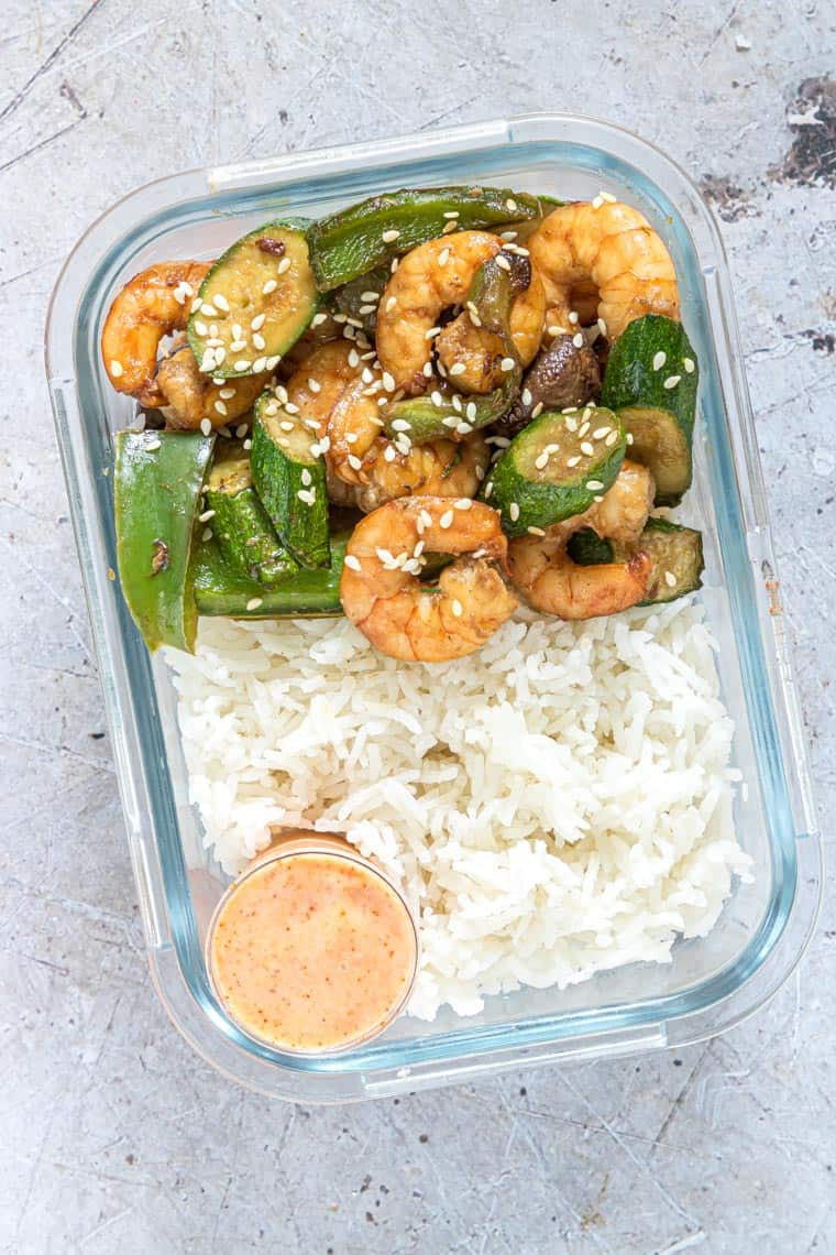 a glass meal prep container filled with rice, hibachi shrimp and a cup of yum yum sauce