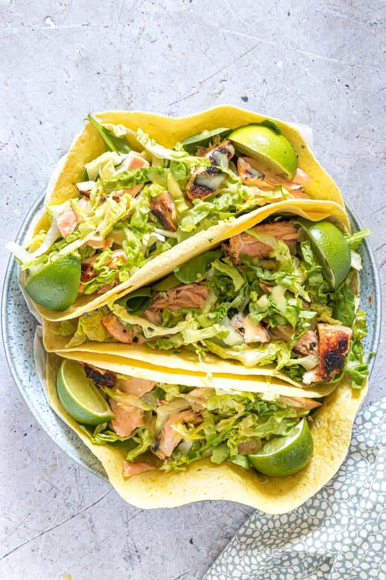 juicy salmon tacos with lettuce, limes and shredded veggies