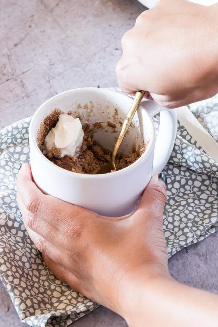hands holding one snickerdoodle mug cake serving