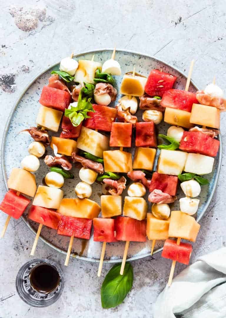 watermelon skewers on a plate with a balsamic drizzle