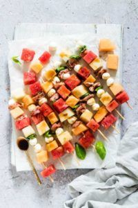 watermelon skewers on a boards with a teaspoon