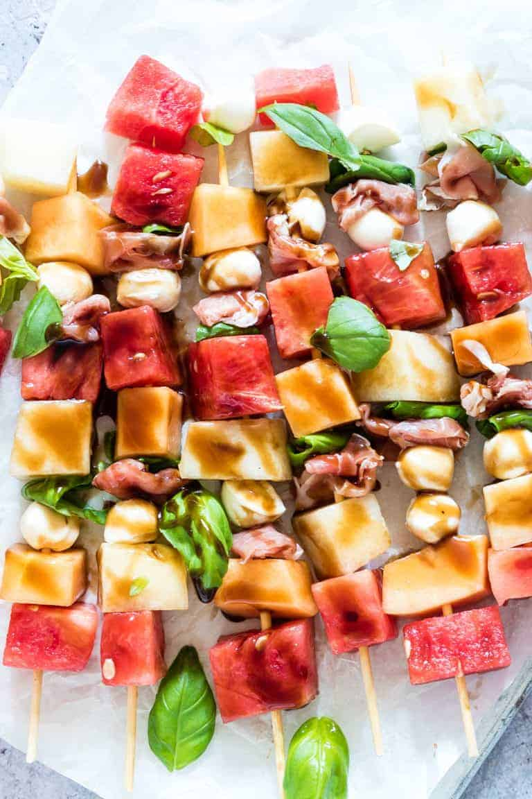 close up of watermelon kabobs with melon, cheese, prosciutto and basil