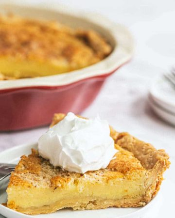 a slice of Bourbon Buttermilk Pie topped with whipped cream