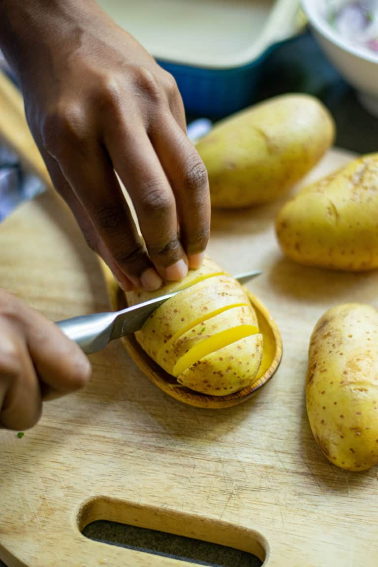 showing potatoes being sliced on a spoon to make hasselback potatoes