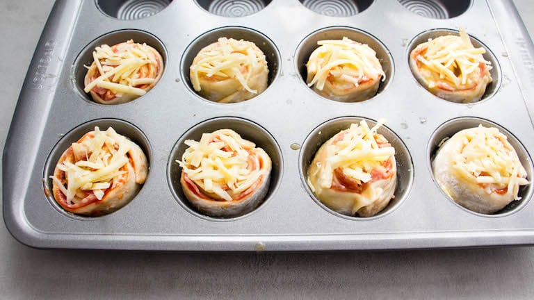 a muffin pan filled with pizza rolls ready to be baked in the oven