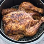 finished air fryer cornish hen inside the air fryer basket