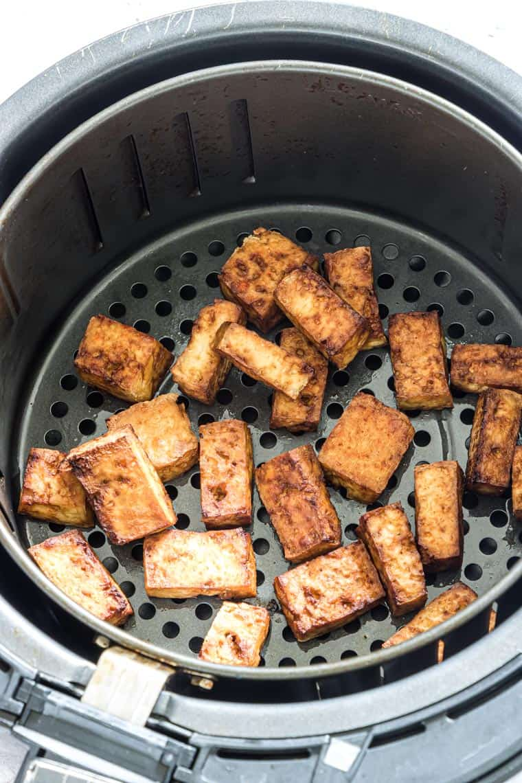 close up view of air fryer tofu inside the air fryer basket