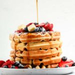 a stack of buttermilk waffles topped with fresh berries, butter and maple syrup