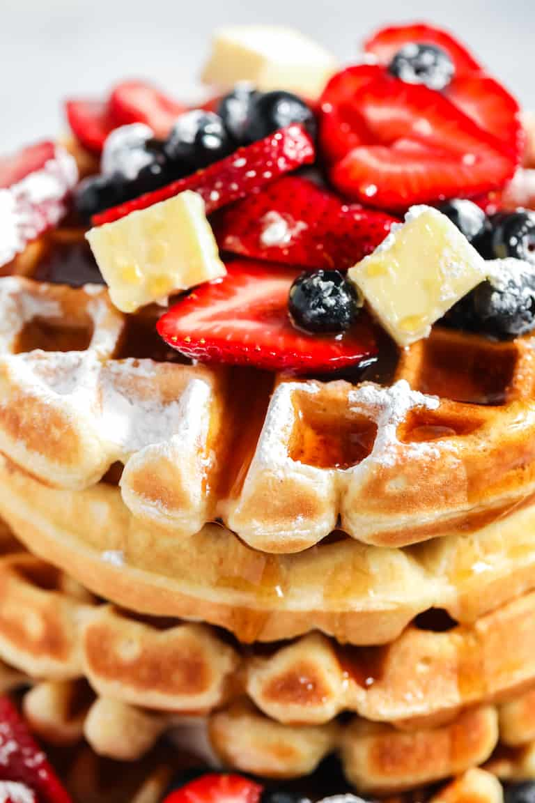 close up view of stacked buttermilk waffles topped with fresh berries