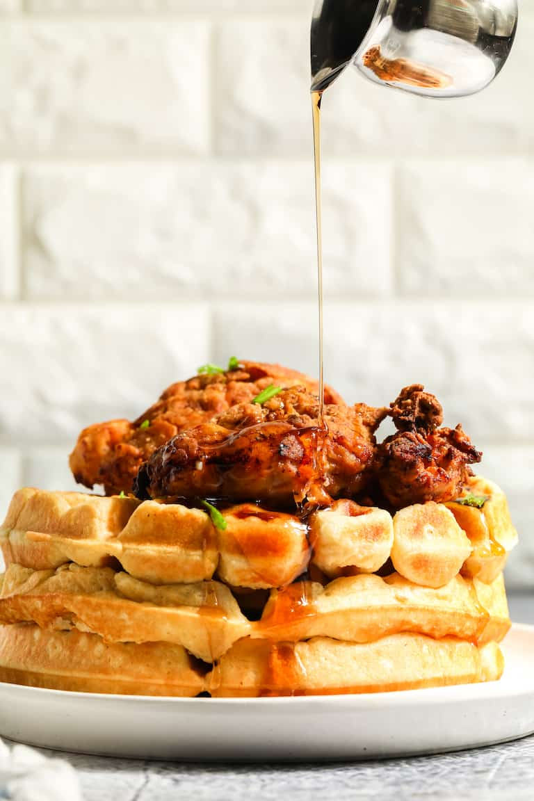 profile view of chicken and waffles with maple syrup being poured on top