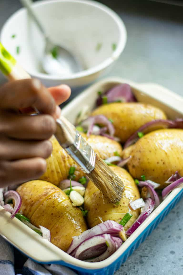 Close up of hasselback potatoes being brushed with seasoned oil