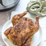 instant pot cornish hen on a white plate and ready to be served