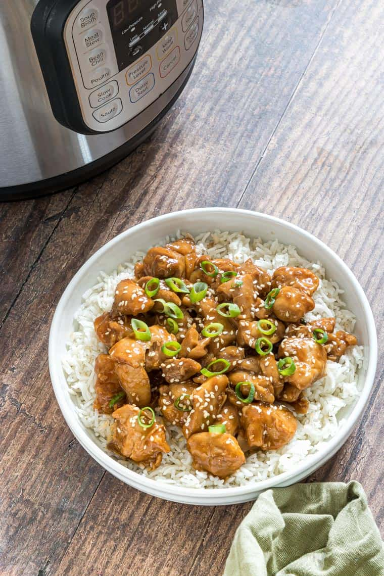a serving of instant pot sesame chicken in a bowl placed in front of the instant pot