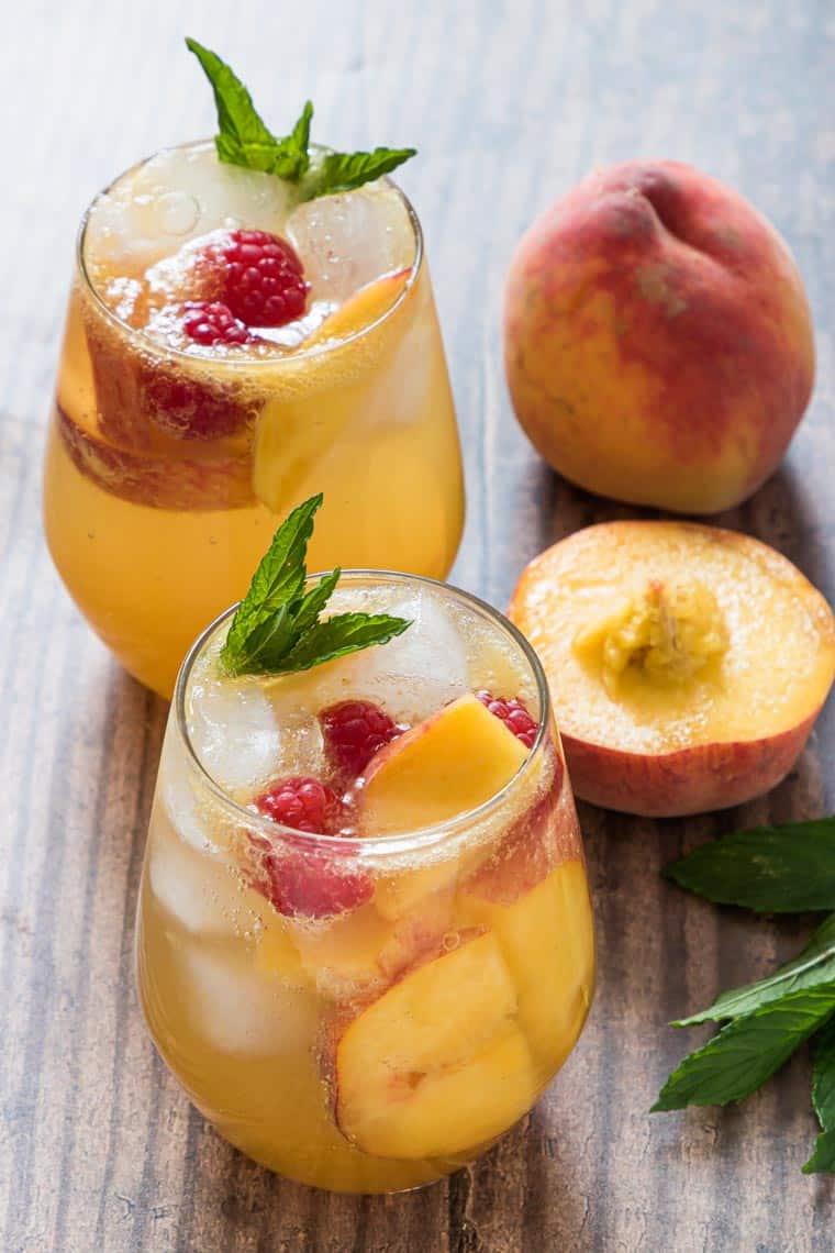 two peach bourbon smash cocktails next to a fresh peach