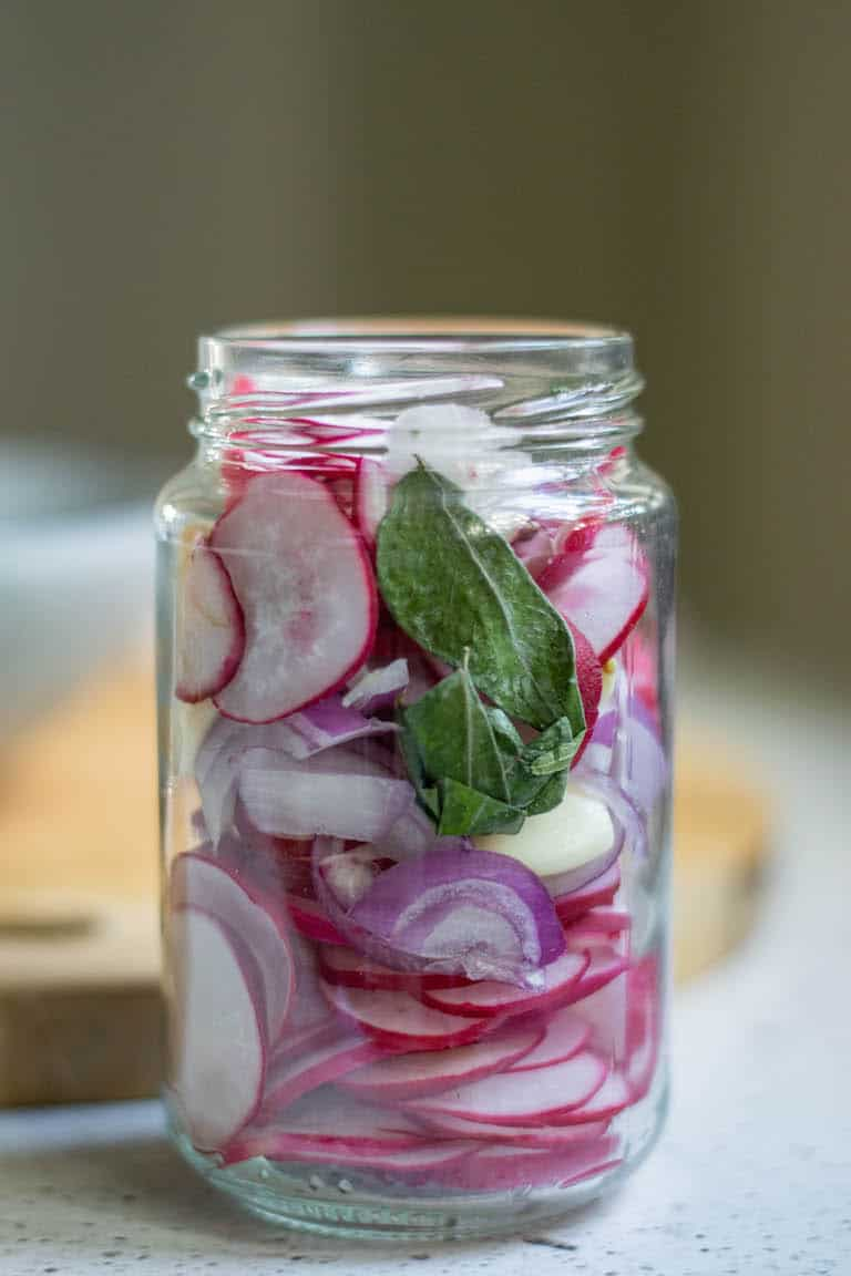 a glass mason jar filled with pickled radishes