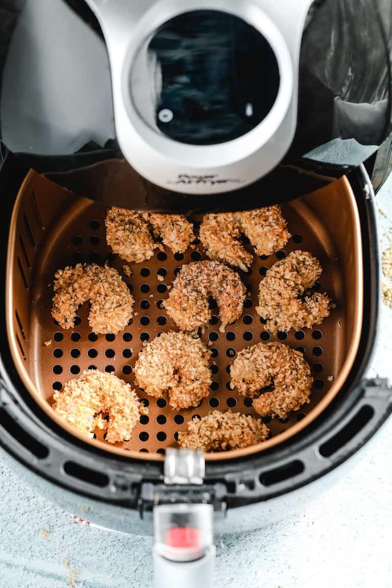 cooked shrimp inside the air fryer basket ready for making shrimp po boy sandwich recipe