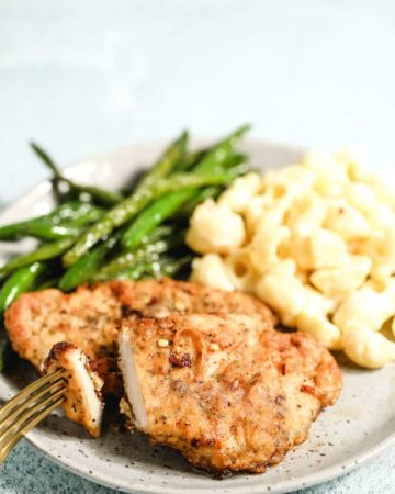 southern fried pork chops and gravy served on a white plate with green beans and mac and cheese