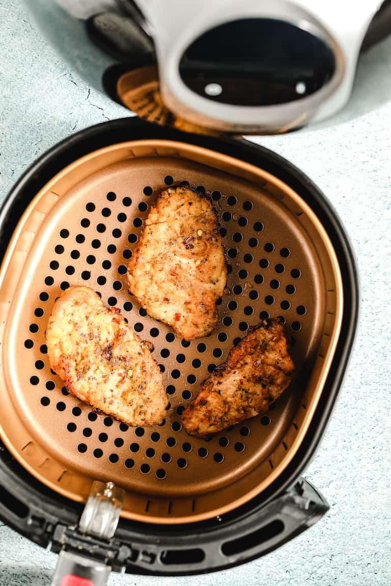fried pork chops inside the air fryer basket