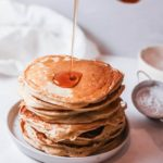 a stack of buttermilk pancakes with syrup being poured on top