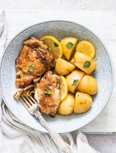 Instant Pot Chicken and Potatoes served in a blue bowl with fork and cloth napkin