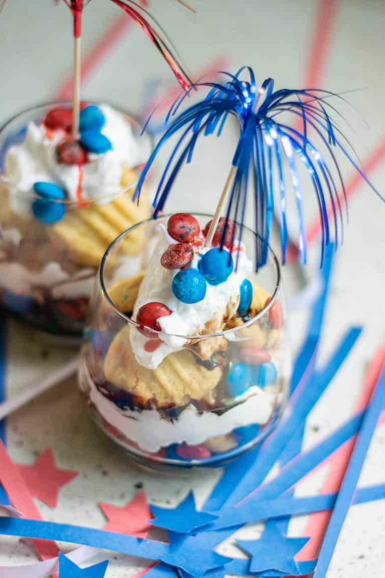 two servings of red white and blue trifle with paper decorations