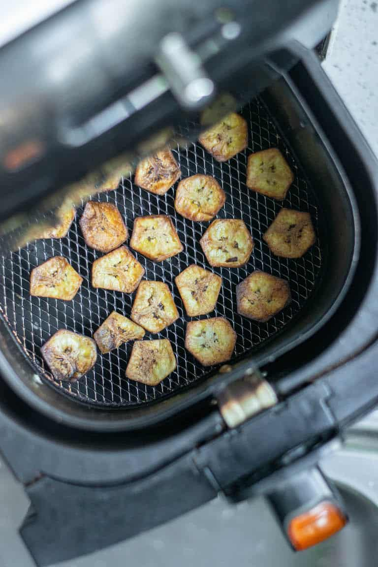 cooked banana chips inside the air fryer basket