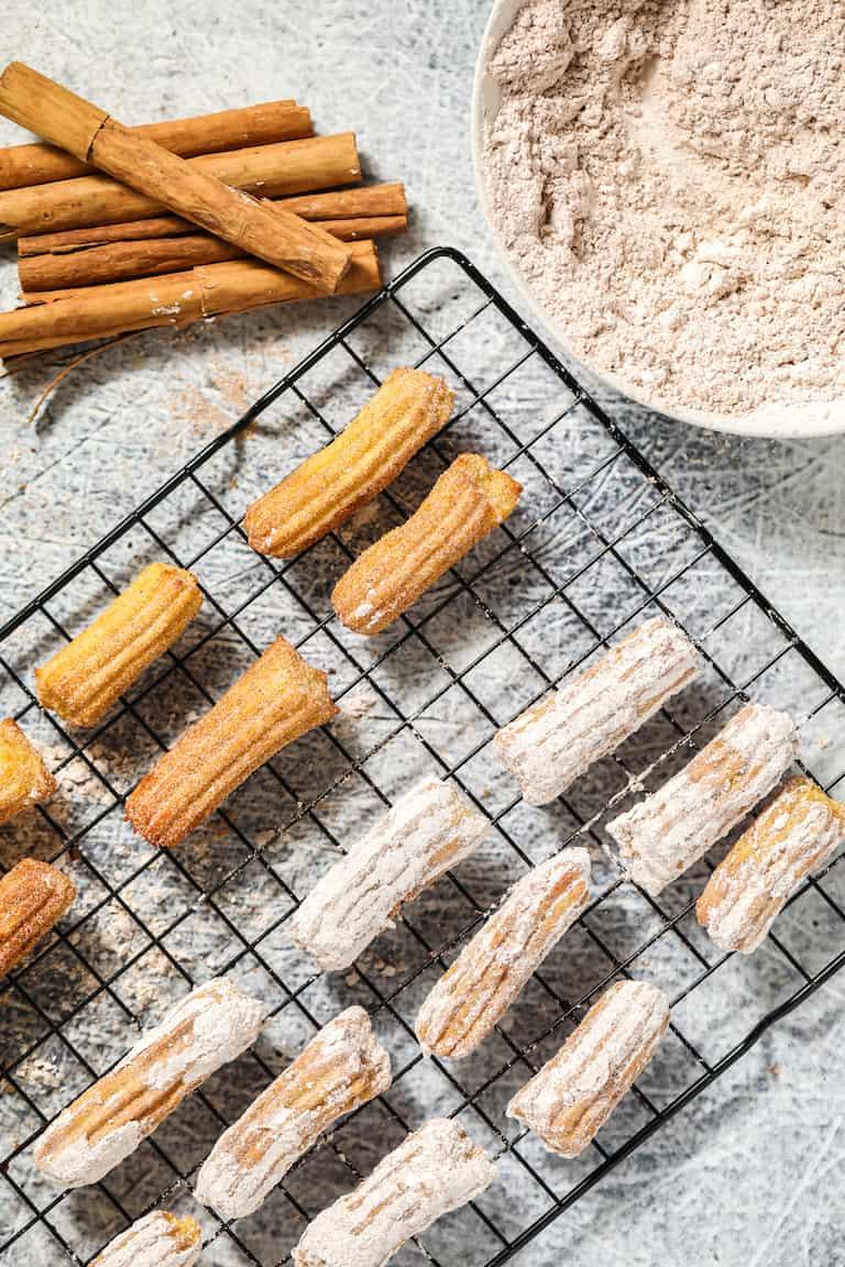air fryer churros on a baking rack being coated in cinnamon sugar