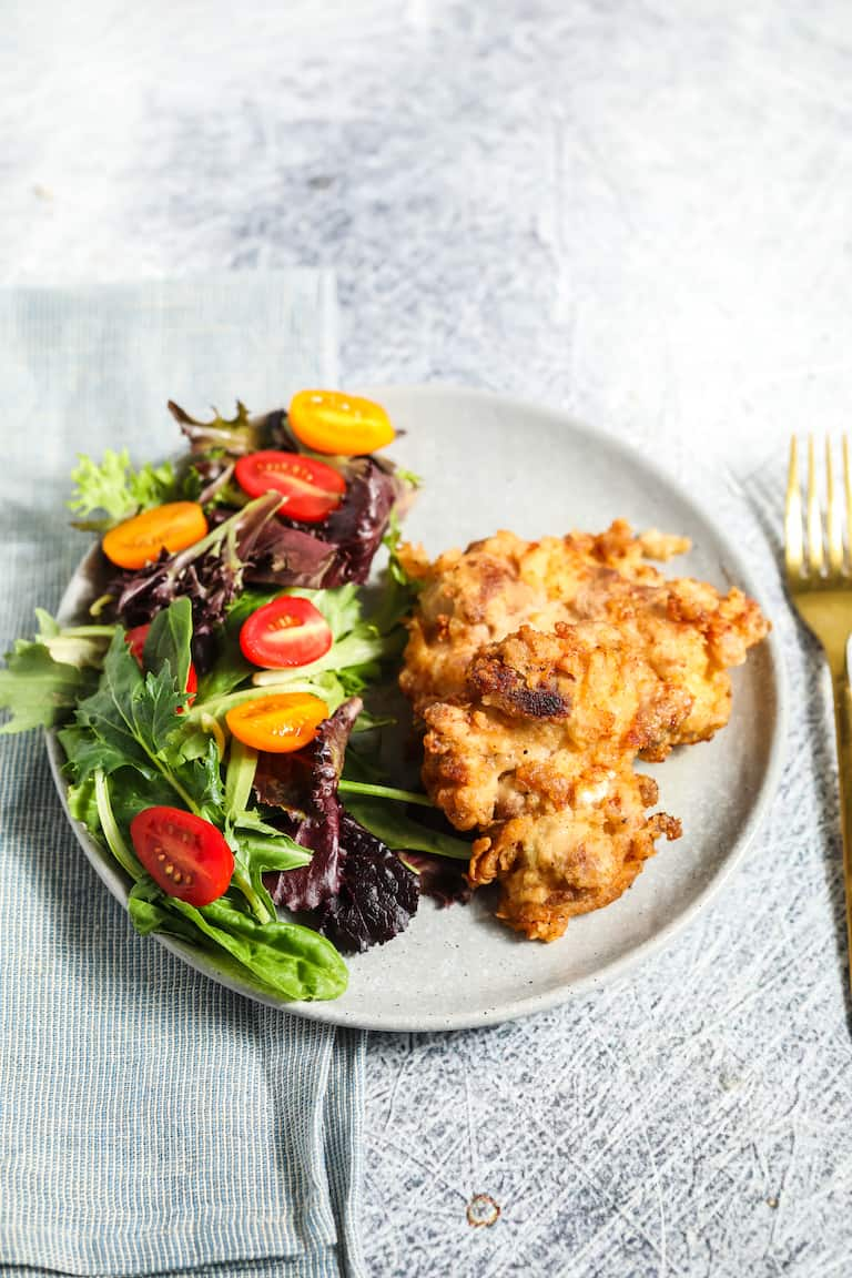 a plate of air fryer fried chicken served with a green salad
