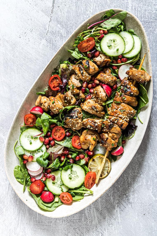 grilled chicken salad served on a white platter