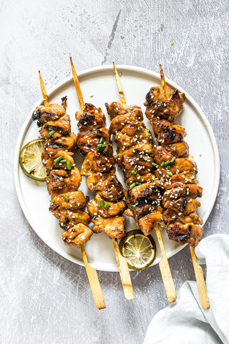 finished grilled chicken skewers on a white plate and garnished with grilled lime slices