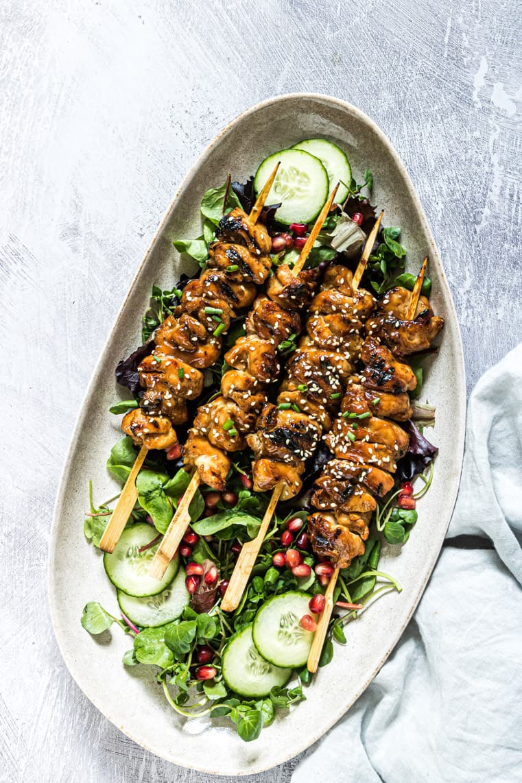 a platter filled with grilled chicken skewers served on top of a green salad