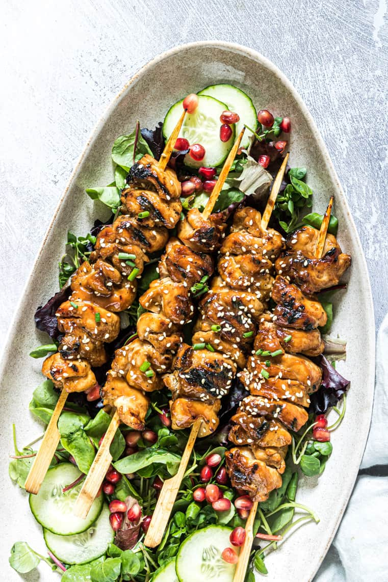 grilled chicken skewers on a bed of lettuce and ready to be served