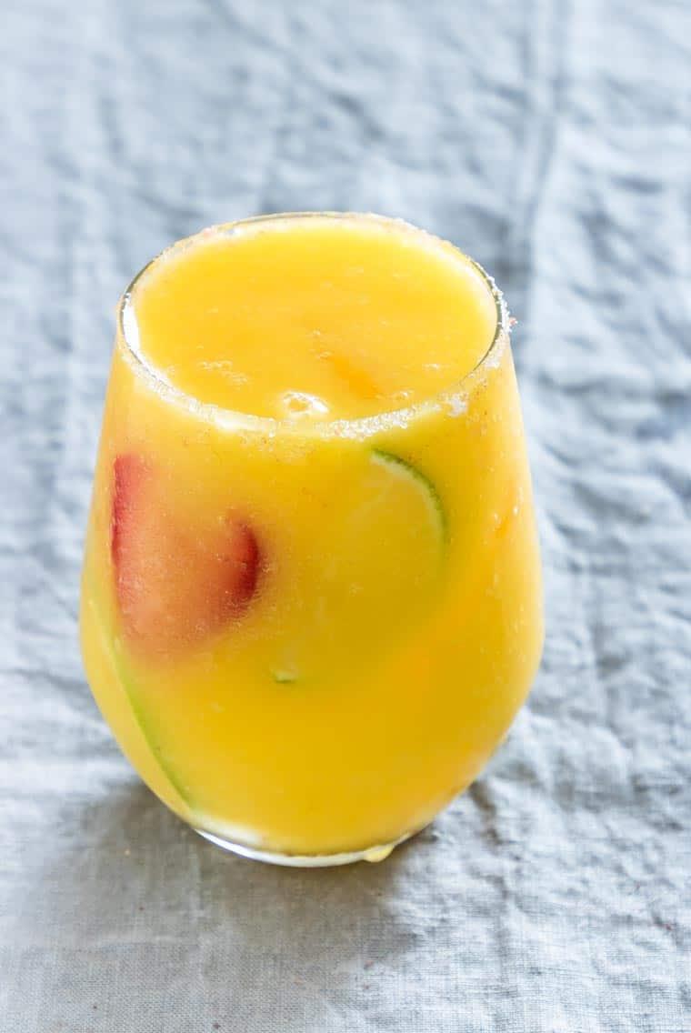 fresh mango margarita garnished with strawberry and ilme