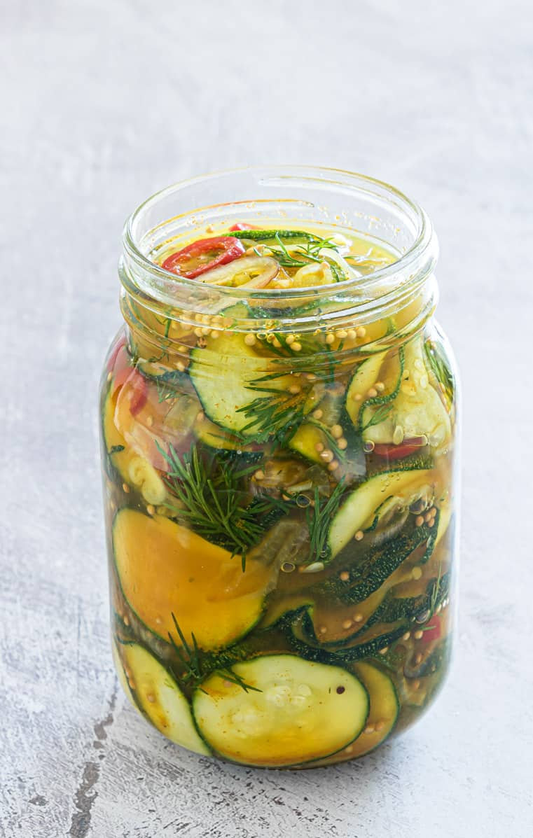 a glass jar filled with pickled zucchini