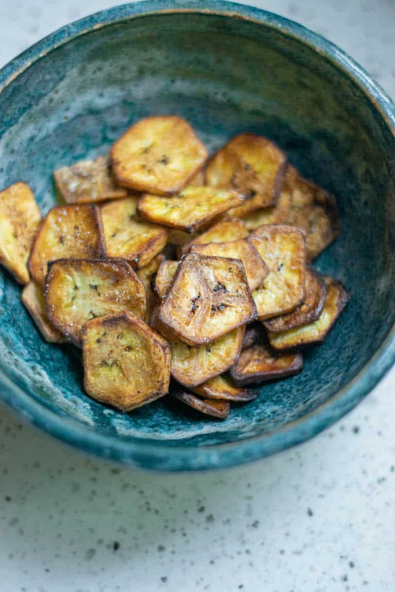 finished plantain chips served in a blue ceramic bowl