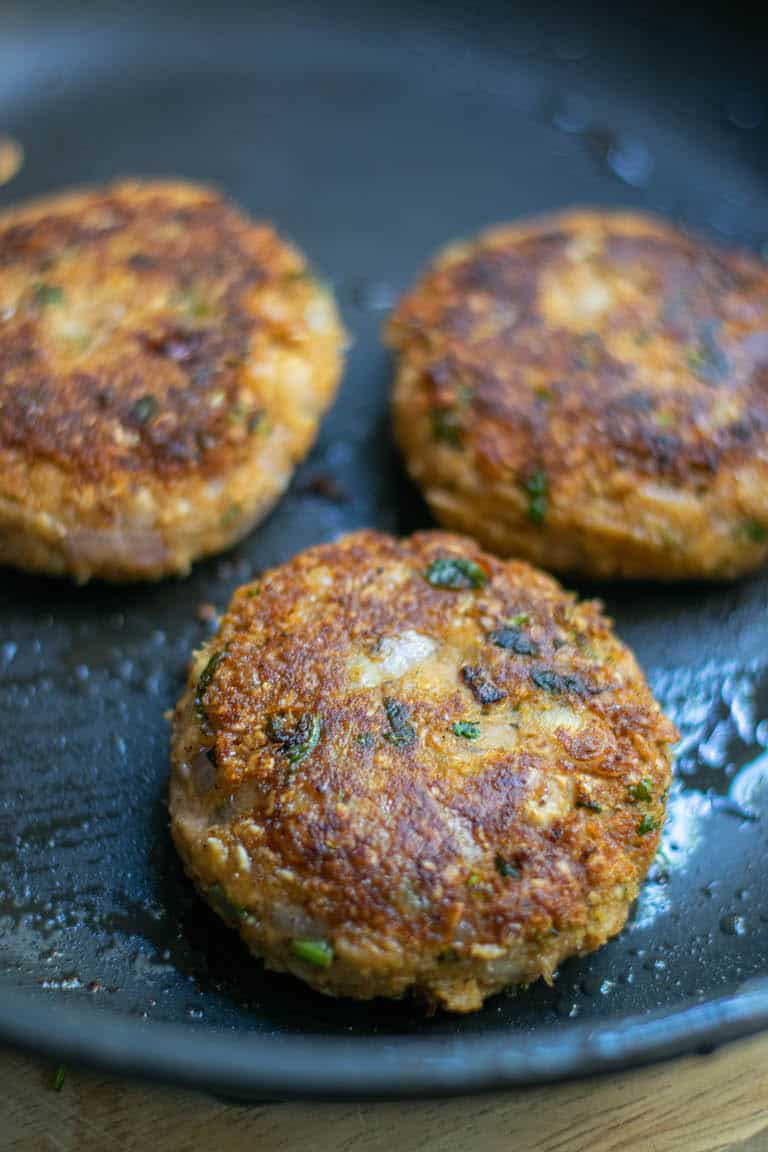 close up of three veggie burger patties in a skillet