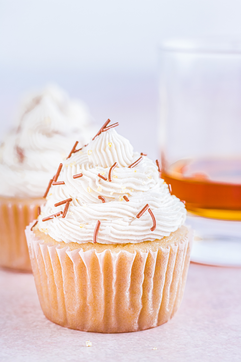 two bourbon spice cupcakes next to a glass of bourbon