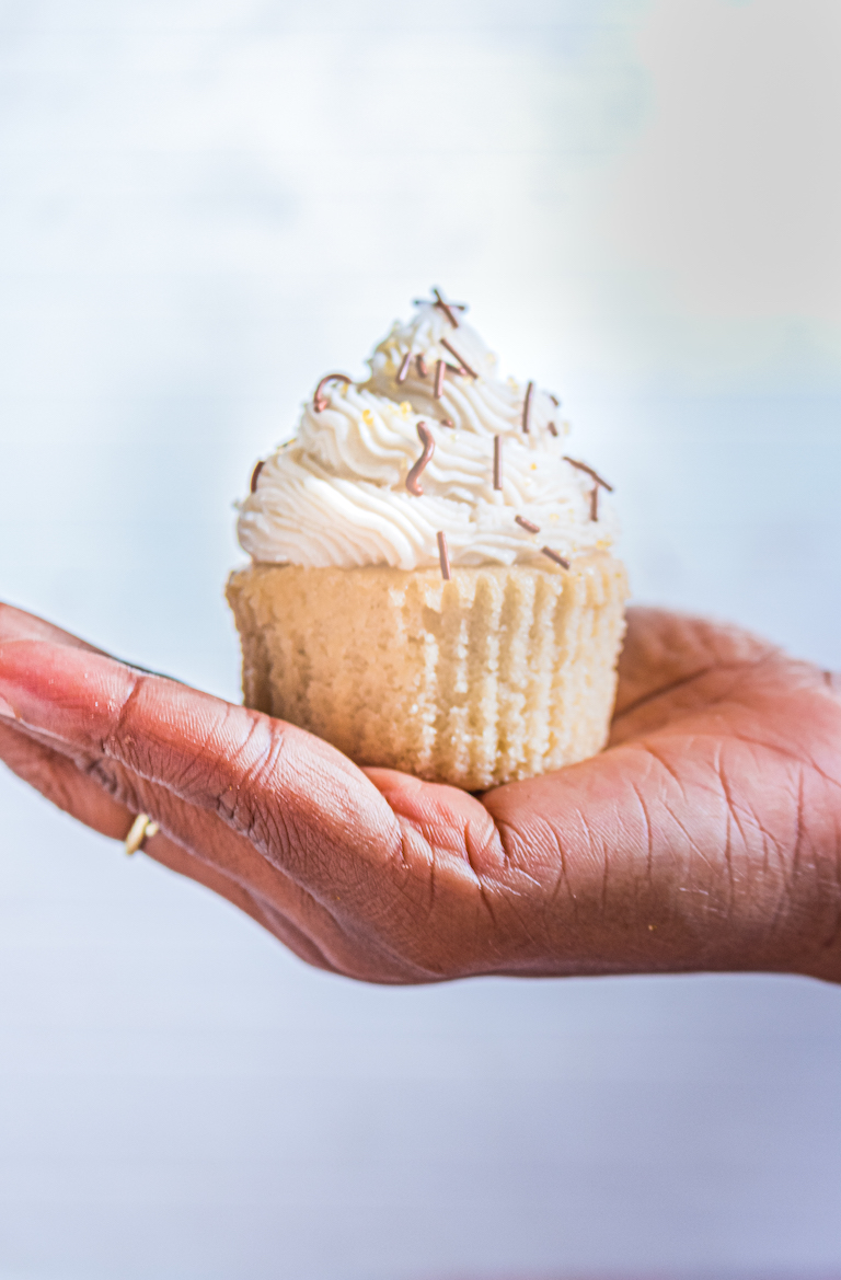 a hand holding one of the bourbon spice cupcakes